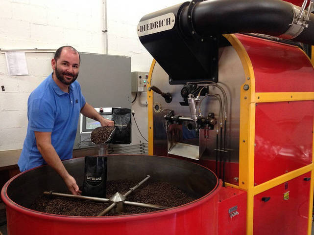 James Axisa packing a bag of Espresso Master coffee beans.